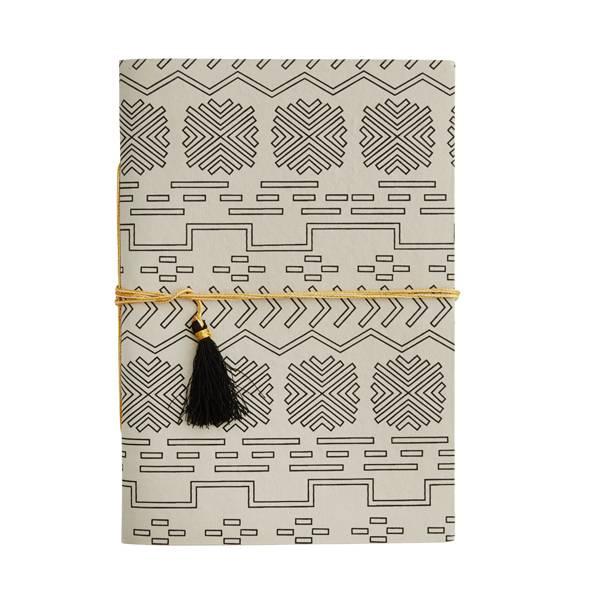 Großes Papier Notebook von Madam Stoltz. In beige und mit schwarzem Muster. 29.5 cm lang und 20 cm breit. Mit gold-schwarzem Band.